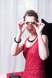 Attractive woman in red dress looking trough magnifying glass Stock Photos