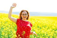 Attractive woman in red dress posing in oilseed rape field royalty free stock photography