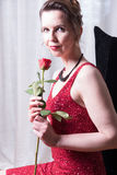 Attractive woman in red dress with rose Royalty Free Stock Photo