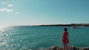Attractive woman in red dress standing on rocky cliff in Mediterranean sea and looking at blue sea water and sky. Drone view of gi. Rl standing on rocks pier at stock footage