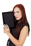 Attractive Woman With Red Hair holds a tablet computer near her Royalty Free Stock Image