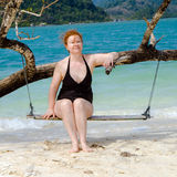 Attractive woman with red hair sits on a swing Royalty Free Stock Photo