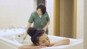 Attractive woman with red lips enjoys a hydromassage in the spa center. Beautiful brunette in bikini lays in the bath in the spa. The doctor makes a hydromassage stock video