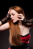 Attractive woman with red long hair on black Stock Images