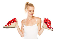 Attractive woman with red sandals. Attractive blonde woman holding up a pair of red sandals in her hands and looking at them with an amused expression Royalty Free Stock Image