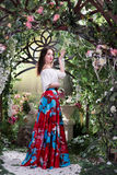 Attractive woman in red skirt in floral garden. Fairy tale Stock Images