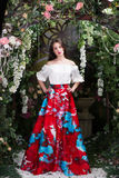 Attractive woman in red skirt in floral garden. Fairy tale Royalty Free Stock Photography