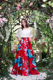 Attractive woman in red skirt in floral garden. Fairy tale Royalty Free Stock Image