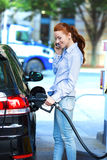 Attractive woman refueling her car at gas station Stock Images