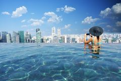 Free Attractive Woman Relaxing And Enjoying The View In Marina Bay Sands Infinity Pool, Singapore, October 16, 2018 Stock Image - 132728541