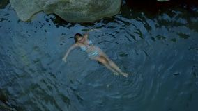 Attractive woman relaxing in clear river water aerial shoot. Young woman swimming in river drone view. Relax and enjoy. Refreshing water on hot day stock video