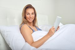 Attractive woman relaxing in comfortable neutral white bed with a tablet computer. In her hands and a friendly smile Stock Images