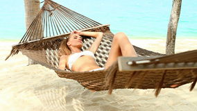Attractive woman relaxing in a hammock stock video footage