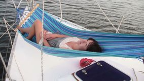 Attractive woman relaxing in hammock on sailing boat, traveling. Stock footage stock footage