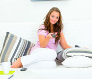 Attractive woman relaxing on sofa and watching TV Royalty Free Stock Photos
