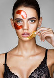 Attractive woman removes color patches with her face. Stock Photos