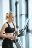 Attractive woman resting after workout on treadmill Royalty Free Stock Images