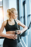 Attractive woman resting after workout on treadmill Royalty Free Stock Photo