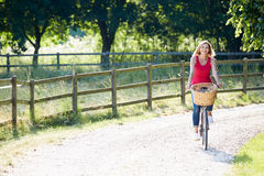 Attractive Woman Riding Bike Along Country Lane. On Her Own Smiling Royalty Free Stock Images
