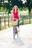 Attractive Woman Riding Bike Along Country Lane. Looking To Camera Smiling Royalty Free Stock Photo
