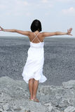 Attractive woman on a rocky beach. Attractive woman in white dress on a rocky beach Royalty Free Stock Images