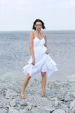 Attractive woman on a rocky beach. Attractive woman in white dress on a rocky beach Royalty Free Stock Photography