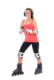 Attractive woman in roller skates listening music on white backg Stock Images