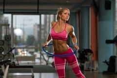 Attractive Woman Rotates Hula Hoop Stock Image