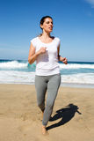 Attractive woman running barefoor on a beach Royalty Free Stock Images