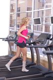 Attractive woman running on treadmill Stock Photo