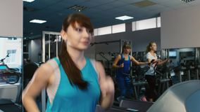 Attractive woman running on a treadmill, smiling. Training at the gym.  stock footage
