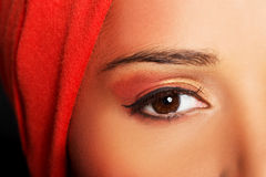 Attractive woman's eye. Woman in turban. Closeup. Isolated on black Stock Image