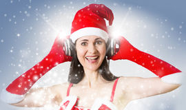 Attractive woman in Santa Clause costume with headset listening Christmas song Royalty Free Stock Photo