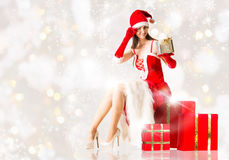 Attractive woman in Santa Clause costume holding Christmas gifts Royalty Free Stock Photos