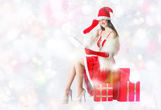 Attractive woman in Santa Clause costume holding Christmas gifts Stock Images