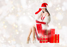 Attractive woman in Santa Clause costume reading Santa's letter Royalty Free Stock Photo