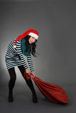 Attractive woman in santa hat with bag Stock Image