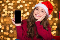 Attractive woman in santa hat holding mobile phone blank screen Royalty Free Stock Image