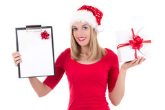 Attractive woman in santa hat with wish list posing isolated on. Young attractive woman in santa hat with wish list posing isolated on white background Royalty Free Stock Image