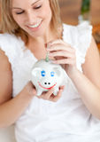 Attractive woman saving money in a piggy-bank Stock Images
