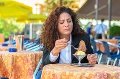 Attractive woman savoring an ice cream sundae Royalty Free Stock Image