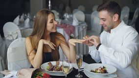 Attractive woman is saying yes to marriage proposal and her boyfriend is putting engagement ring on her finger and. Attractive young woman is saying yes to stock footage