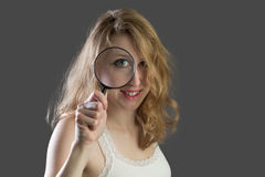 Attractive woman scoping through a magnifying glass Stock Photo