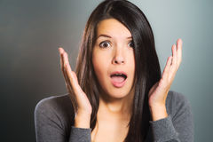 Attractive woman screaming in terror. With her hands to her cheeks, mouth open and frightened wide eyes, close up facial portrait Stock Images