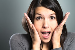 Attractive woman screaming in terror. With her hands to her cheeks, mouth open and frightened wide eyes, close up facial portrait Stock Photography