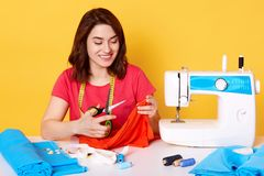 Attractive woman seamstress tailor sitting attable with sewing machine on yellow background in studio. Young dressmaker cuts piese. Of cloth for new dress royalty free stock images