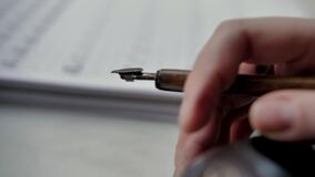 Attractive woman seating next to sheet of paper, fountain pen is in her hand. Writer thinking, dreaming. Loop video