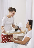 Attractive woman serving breakfast in bed. Royalty Free Stock Images