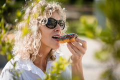 Attractive woman in shades eating doughnut Royalty Free Stock Photos