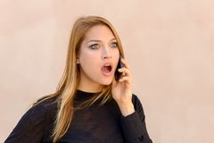 Attractive woman with a shocked expression. Chatting on her mobile phone staring ahead with mouth agape and wide eyes stock image